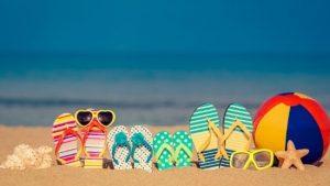 Slippers en zonnebrillen in het zand